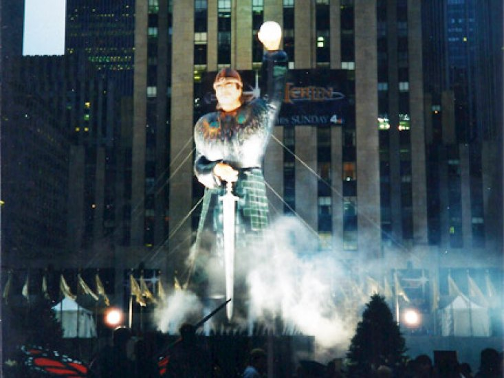 100' tall Merlin standing in Rock Center